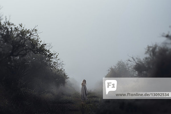 Girl standing on field against clear sky while being wrapped in blanket during foggy weather