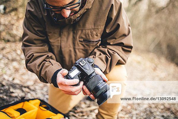 Männlicher Wanderer stellt Kamera ein  während er auf einem Feld im Wald kniet