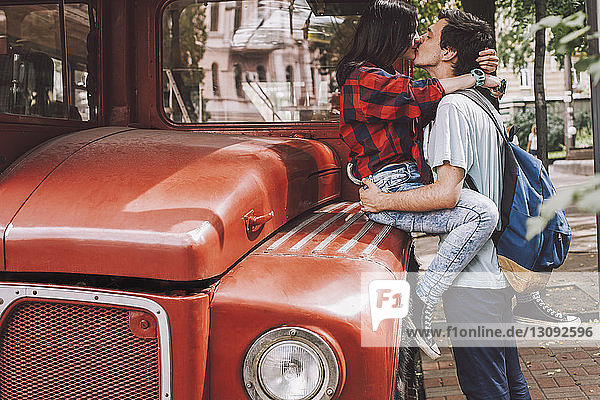 Side view of young couple kissing on mouth in city by vintage bus