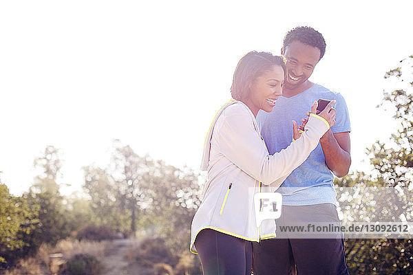 Ein glücklicher Mann und eine glückliche Frau telefonieren  während sie auf dem Feld vor klarem Himmel stehen
