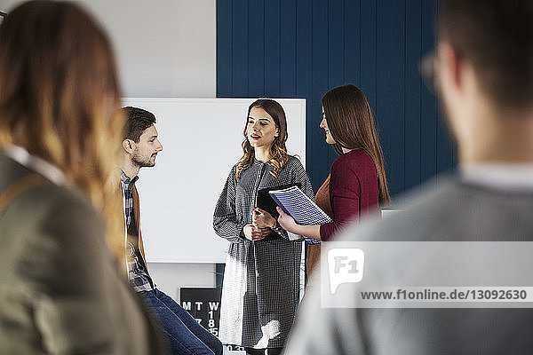 College students talking while standing in classroom