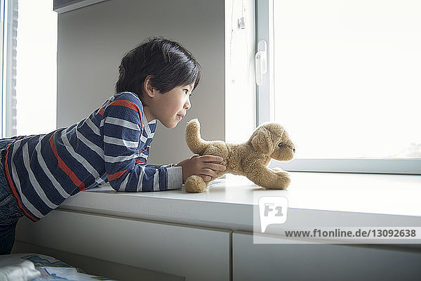 Boy playing with stuffed toy on window sill at home