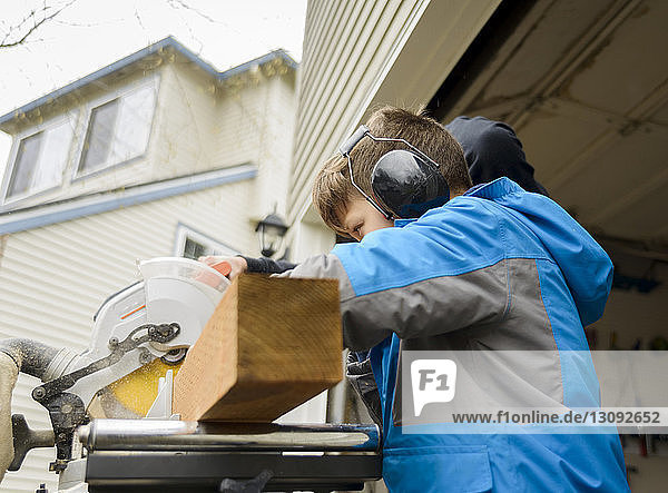 Side view of boy using ear protectors while working at backyard
