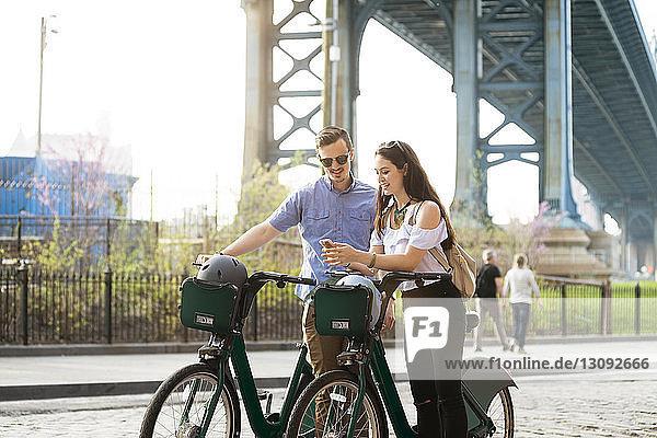 Glückliches Paar steht mit Fahrrädern vor der Manhattan-Brücke und sieht das Telefon an