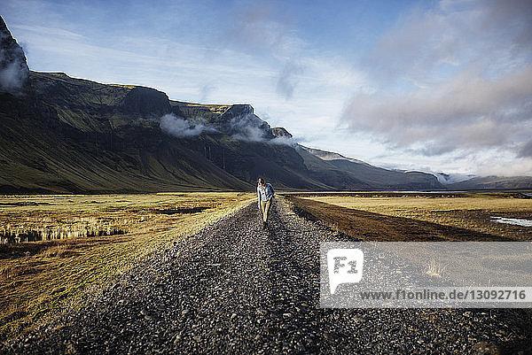 Frau geht auf Feldweg mitten im Feld gegen Berge und Himmel