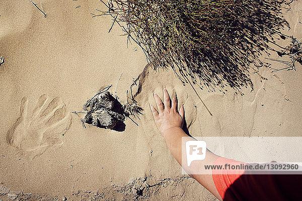 Beschnittenes Bild eines Jungen  der Handabdrücke auf Sand macht