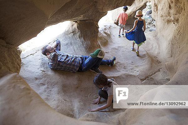 Vater entspannt sich  während die Kinder in der Höhle spielen