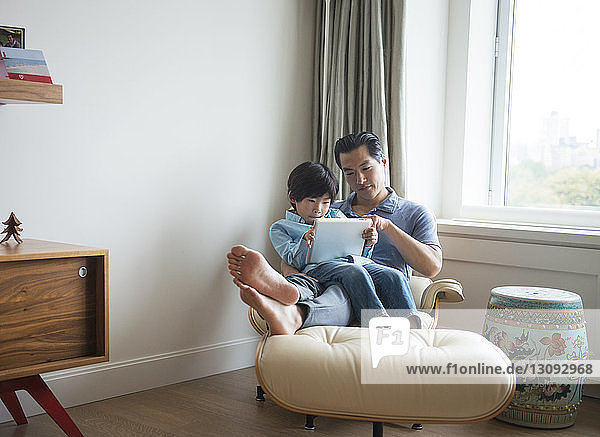Father and son using tablet while sitting against window at home