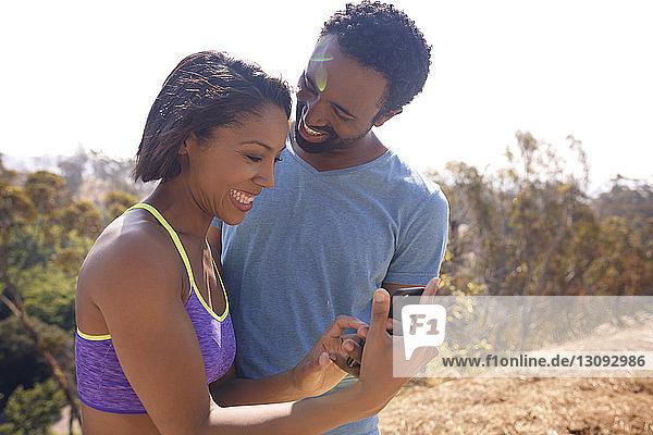 Glückliches Paar beim SMS-Versand im Stehen auf dem Feld vor klarem Himmel