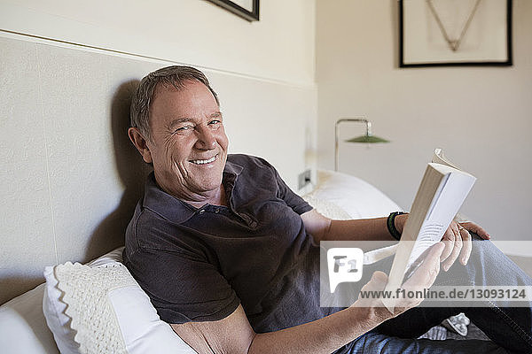 Portrait of happy senior man holding book while sitting on bed at home