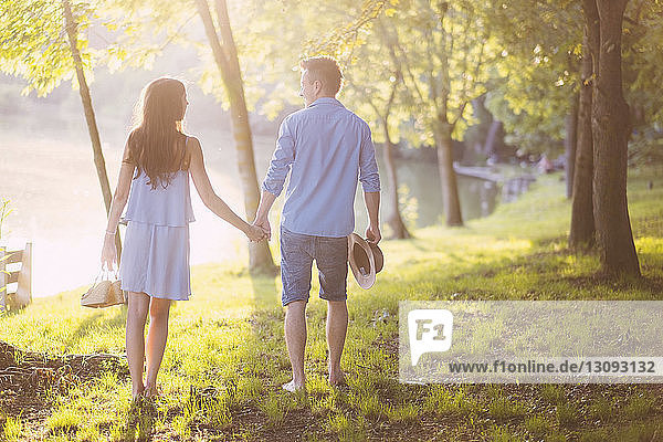 Rear view of couple holding hands while walking on grassy field at park
