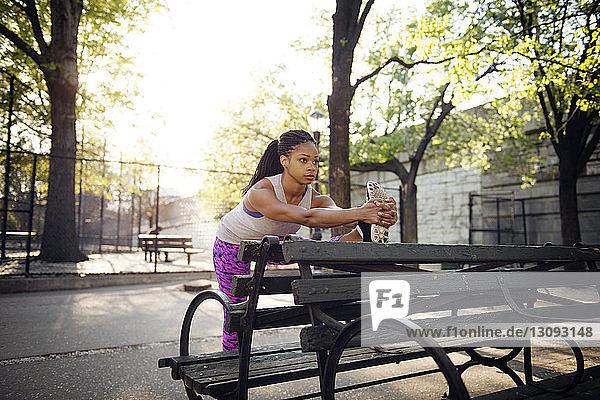 Frau streckt sich auf Holzbank im Park