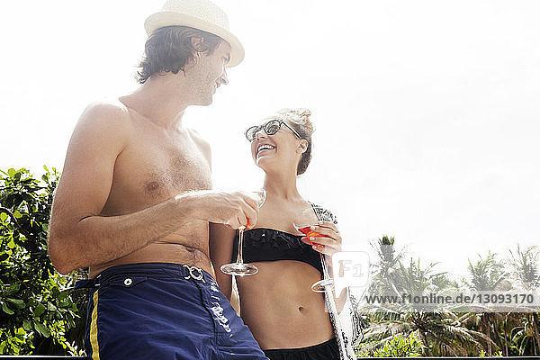 Niedrigwinkelansicht eines glücklichen Paares  das am Urlaubsort Getränke gegen den klaren Himmel hält