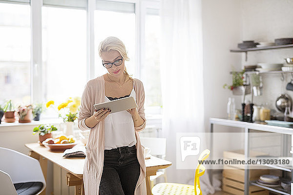Woman using tablet computer while standing at home