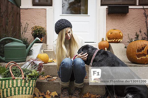 Frau spielt mit Hund  während sie auf Stufen sitzt