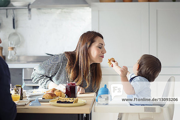 Man looking at son feeding mother at table in kitchen