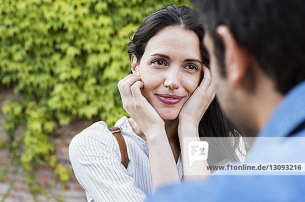 Lächelnde Frau schaut Mann gegen Efeuwand