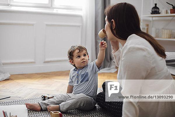 Säugling sieht Mutter an  die zu Hause aus Spielzeug-Teetasse trinkt