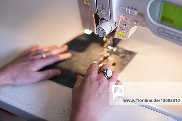 Beschnittenes Bild einer Schneiderin  die eine Nähmaschine bei Tisch in der Werkstatt benutzt