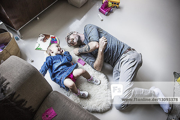 High angle view of happy father and daughter lying on floor at home