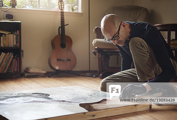 Man painting while sitting at home