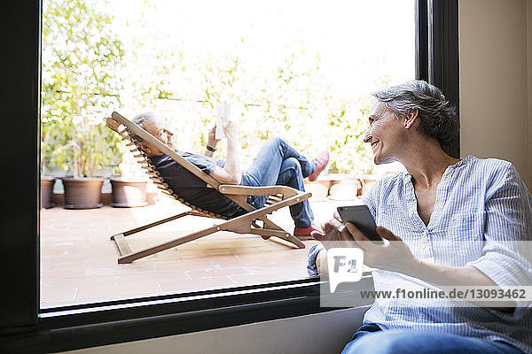 Happy woman looking at senior man sitting on deck chair at porch