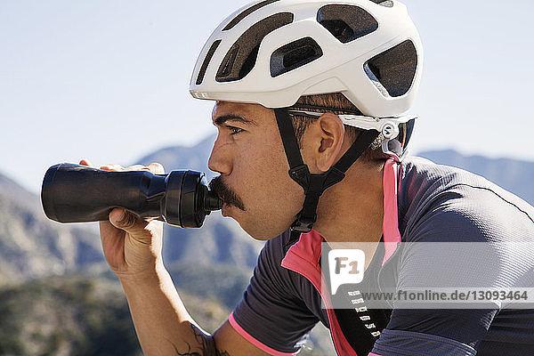 Nahaufnahme eines Mountainbikers  der aus der Flasche trinkt