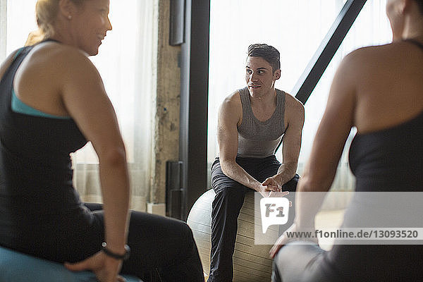 Male instructor looking away while sitting with women on fitness balls in gym