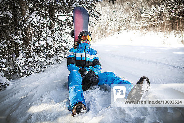 Man with snowboard relaxing on snow covered field