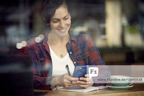 Lächelnde Frau mit Kaffee und Buch auf dem Tisch mit einem Mobiltelefon im Café durch ein Fenster gesehen