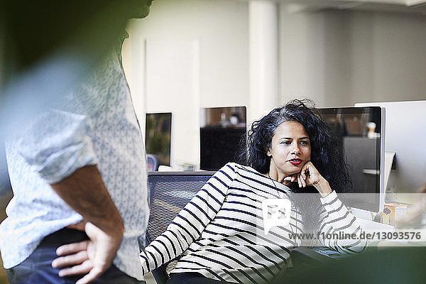 Geschäftsfrau mit Hand am Kinn  die am Schreibtisch sitzend von einem männlichen Kollegen im Büro wegschaut
