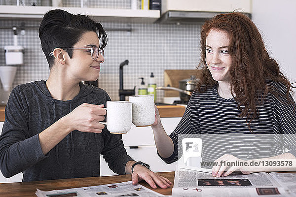 Lesbian couple toasting coffee cups at table
