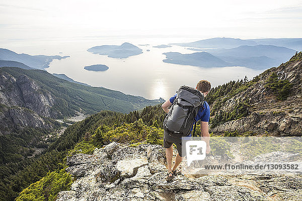 Hochwinkelaufnahme eines Wanderers mit Rucksack auf dem Berg gegen den Himmel