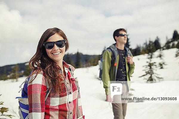Glückliche Freunde wandern auf schneebedecktem Feld gegen wolkigen Himmel