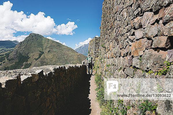 Rückansicht eines Wanderers  der an alten Ruinen vorbeigeht  gegen den Himmel bei Pisac