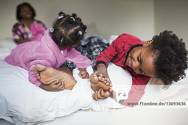Children tickling father's feet on bed