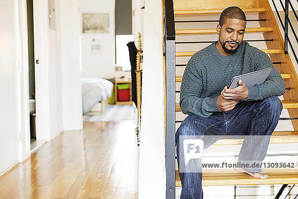 Mann benutzt einen Tablet-Computer  während er zu Hause auf einer Treppe sitzt