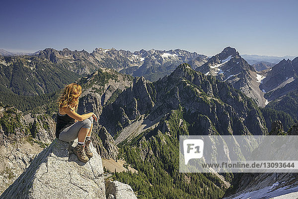 Hiker looking at view while sitting on mountain against clear sky during sunny day