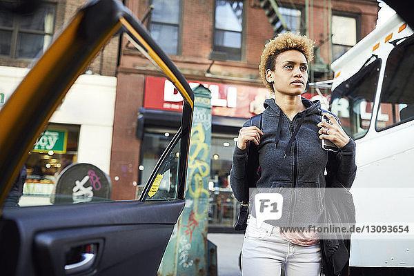 Nachdenkliche junge Frau trägt Rucksack  während sie inmitten von Fahrzeugen auf der Straße der Stadt steht