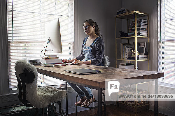 Young woman using computer at table in office