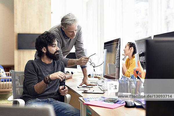 Geschäftsleute diskutieren über Desktop-Computer mit einer im Hintergrund sitzenden Kollegin