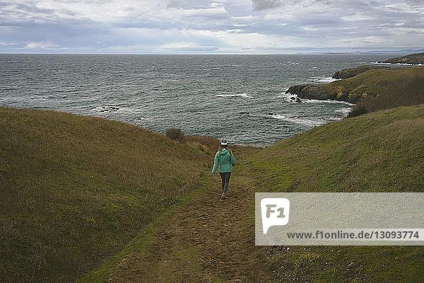 Rear view of woman walking towards sea on field against cloudy sky