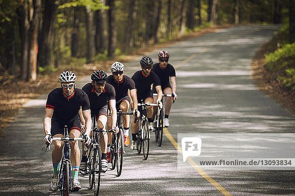 Cyclists riding bicycles in row on country road