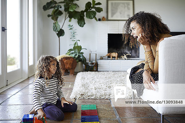 Mother with mouth open looking at daughter playing with toy blocks in living room