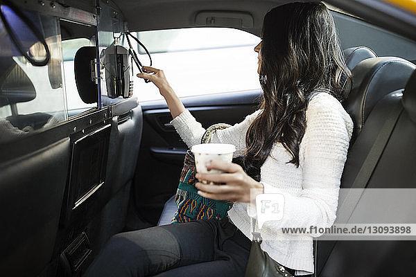 Junge Frau hält Einwegglas in der Hand  während sie im Taxi kontaktlos per Smartphone bezahlt