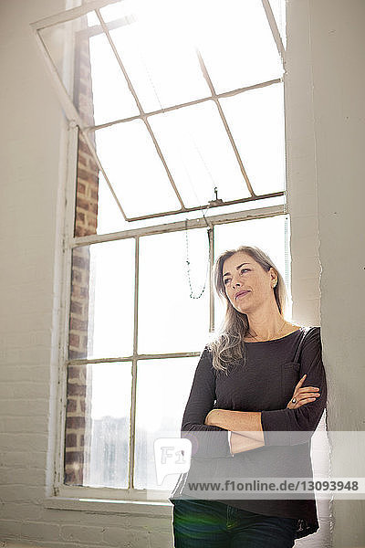 Thoughtful woman with arms crossed leaning on wall at home