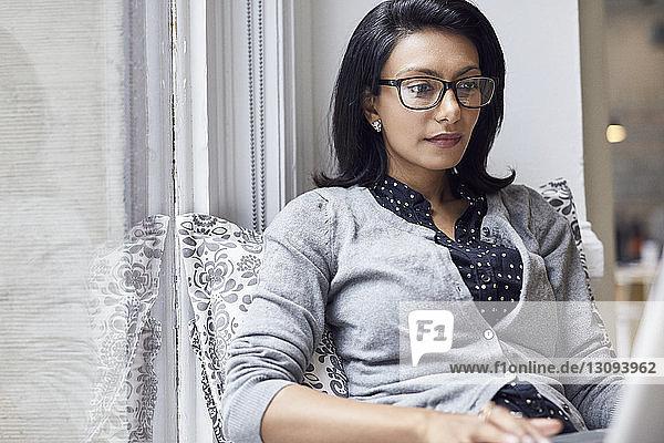 Geschäftsfrau  die am Laptop arbeitet  während sie im Büro sitzt