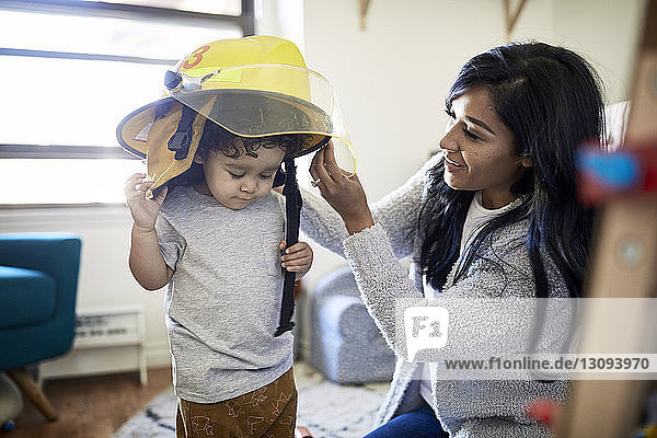 Mother putting firefighter's helmet on son at home