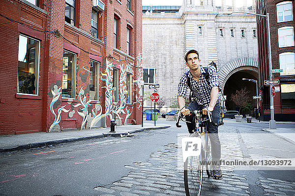 Man looking away while riding bicycle on street against buildings