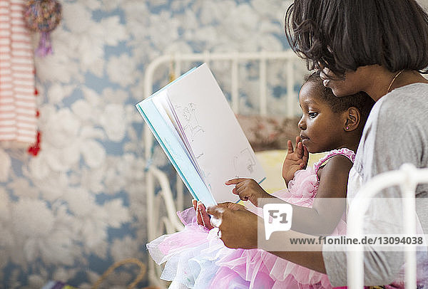 Girl pointing at picture book while sitting with mother in bedroom